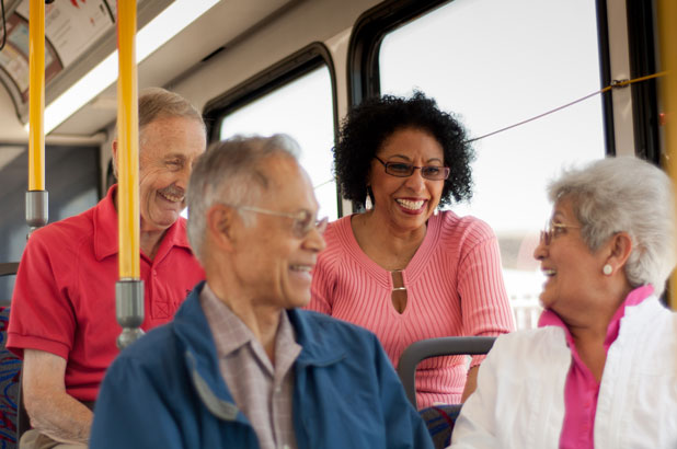 Four seniors happily riding the bus together